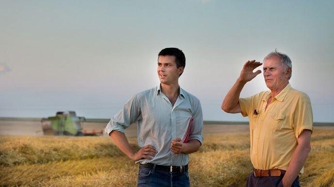 jeune et vieil agriculteurs dans des champs